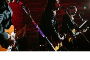 band on stage with mics and guitars