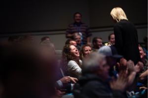 woman in audience laughing